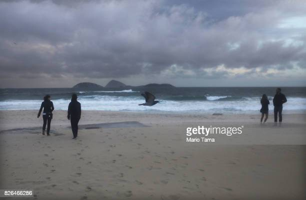 People are bundled up against the cold on Ipanema beach in the midst of a winter cold front on August 4 2017 in Rio de Janeiro Brazil Temperatures...