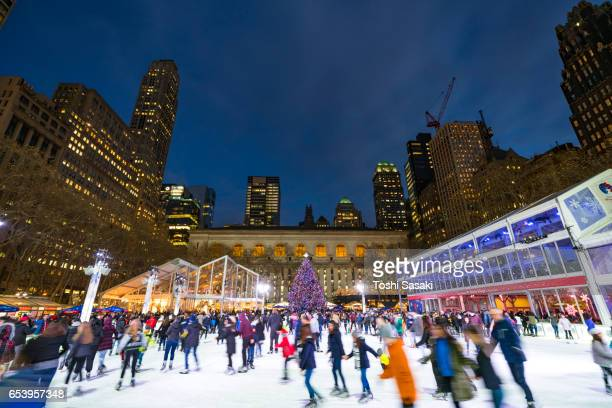 People are enjoying Ice Skating at Bryant Park New York in dusk at Christmas Holidays Season on Dec. 28 2016. A Christmas tree stands at front of New York City Library.