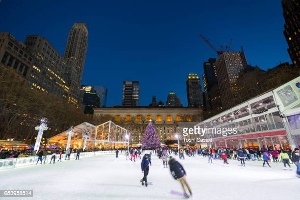 People are enjoying Ice Skating at Bryant Park New York in dusk at Christmas Holidays Season on Jan. 012017. A Christmas tree stands at front of New York City Library.