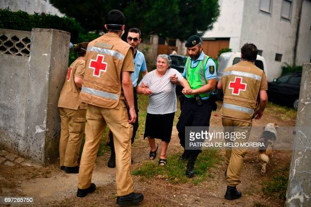 TOPSHOT People are evacuated from their houses by Red Cross and police members due the proximity of a dangerous wildfire at Torgal Castanheira de...