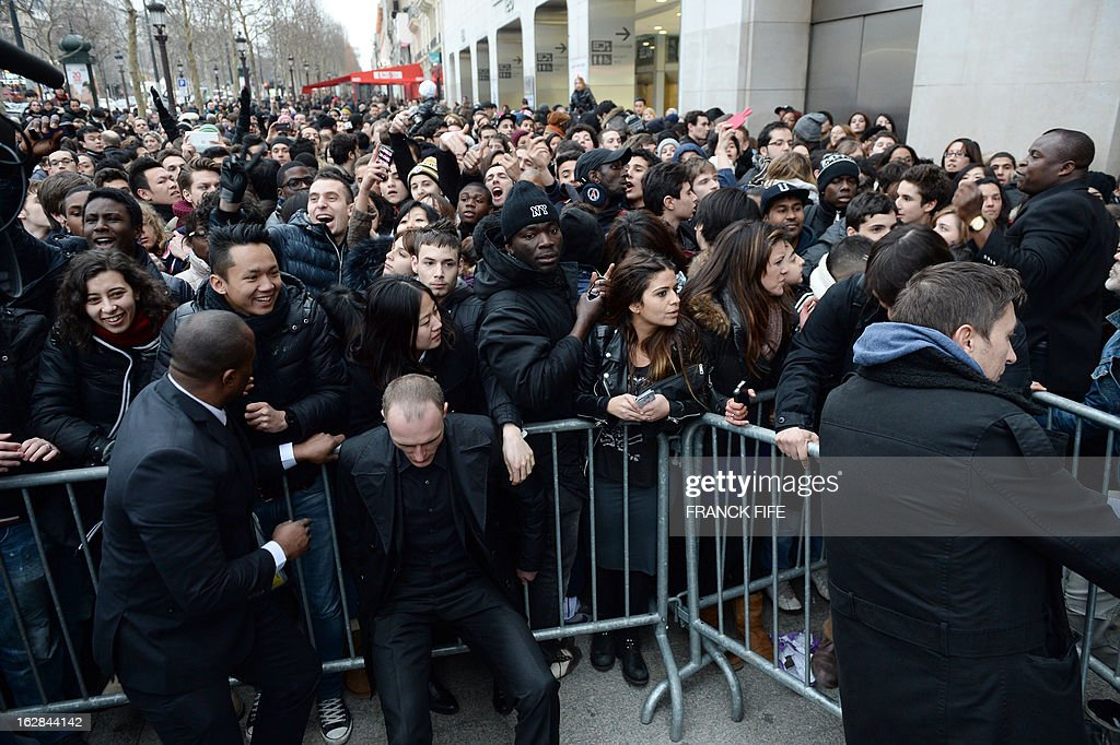 People are gathered in front of a store on the Champs-Elysees avenue in Paris, on February 28, 2013, where Paris Saint-Germain's (PSG) English midfielder David Beckham meets fans. Beckham and French former international player Zinedine Zidane have autographed balls and jerseys for thirty fans selected via Twitter.