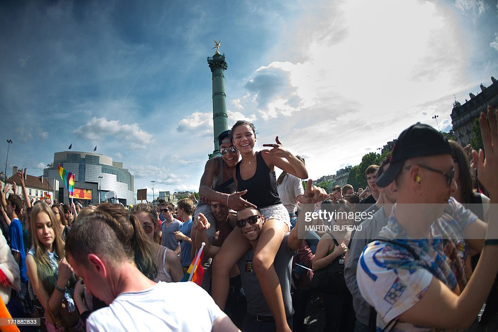 People are gathered on the Bastille square during the homosexual, lesbian, bisexual and transgender (HLBT) visibility march, the Gay Pride, on June 29, 2013 in Paris, exactly one month to the day since France celebrated its first gay marriage. AFP PHOTO / MARTIN BUREAU