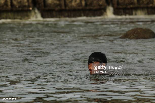 People are looking for oysters at a river mouth in Lhokseumawe on September 20 2017 in Aceh province Indonesia Oysterseeking activities become the...