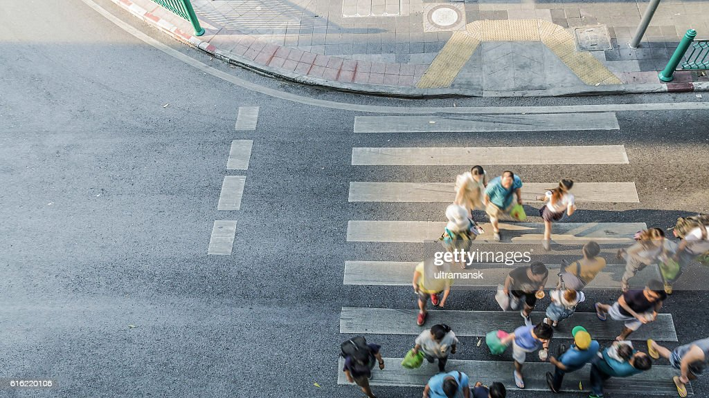People are moving across crosswalk  in the city : Stock Photo
