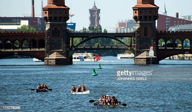 People are pictured in boats on the river Spree near the bridge 'Oberbaumbruecke' in Berlin on July 23 2013 Meteorologists forecast high temperatures...