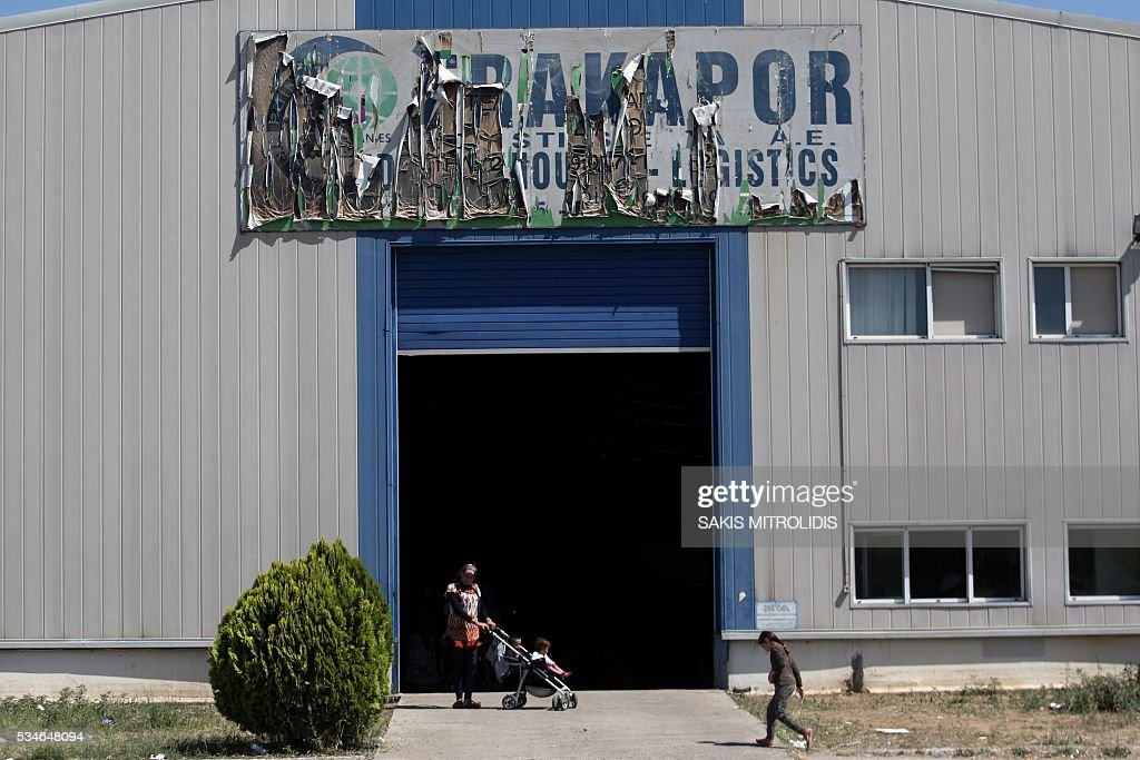 People are pictured inside a new camp for refugees and migrants set in an abandoned factory in Sindos, a west suburb of Thessaloniki on 27 May, 2016. The squalid Idomeni refugee camp in northern Greece which became a symbol of Europe's migrant crisis has been fully evacuated, police said Thursday, as another 30 died crossing the Mediterranean. In the space of three days, police transferred about 4,000 migrants by bus from Idomeni to newly created camps in the industrial outskirts of Greece's second city Thessaloniki. / AFP / SAKIS