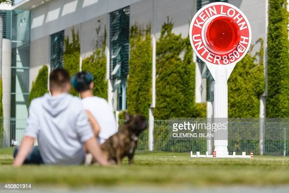People are pictured next to a sign reading 'no wage under 850 Euro' in front of the German parliament during the weekly cabinet meeting at the...