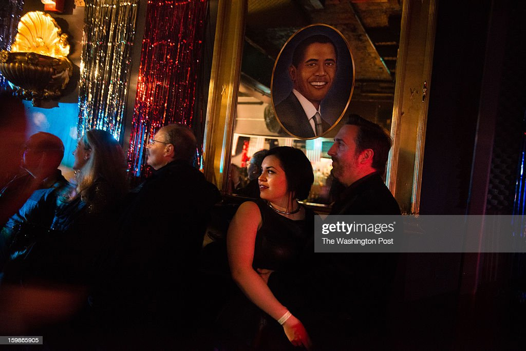 People are pictured under a photo of Obama. The 2013 Artist's Inaugural Ball featured live music, fire performances, Djs, dancing, a hookah lounge and more. It was spread among six areas in the Rock and Roll Hotel and Gallery O on H. A portion of the proceeds went to local charities, Miriam's Kitchen and One Common Unity. The hosts were Mischief, Rogue Wave Project, Artomatic, and Meso Creso.