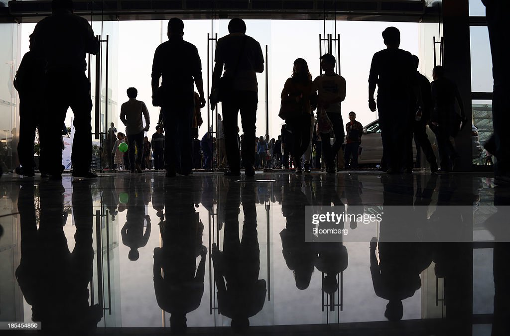 People are reflected as the walk through the an entrance to the Wuhan Motor Show 2013 in Wuhan, China, on Saturday, Oct. 19, 2013. The show will be held through Oct. 23. Photographer: Tomohiro Ohsumi/Bloomberg via Getty Images