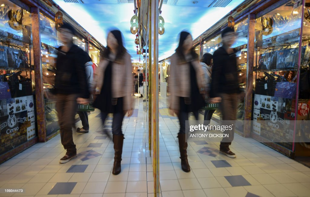People are reflected in a mirror as they pass through a shopping mall in Hong Kong on January 12, 2013. AFP PHOTO / Antony DICKSON