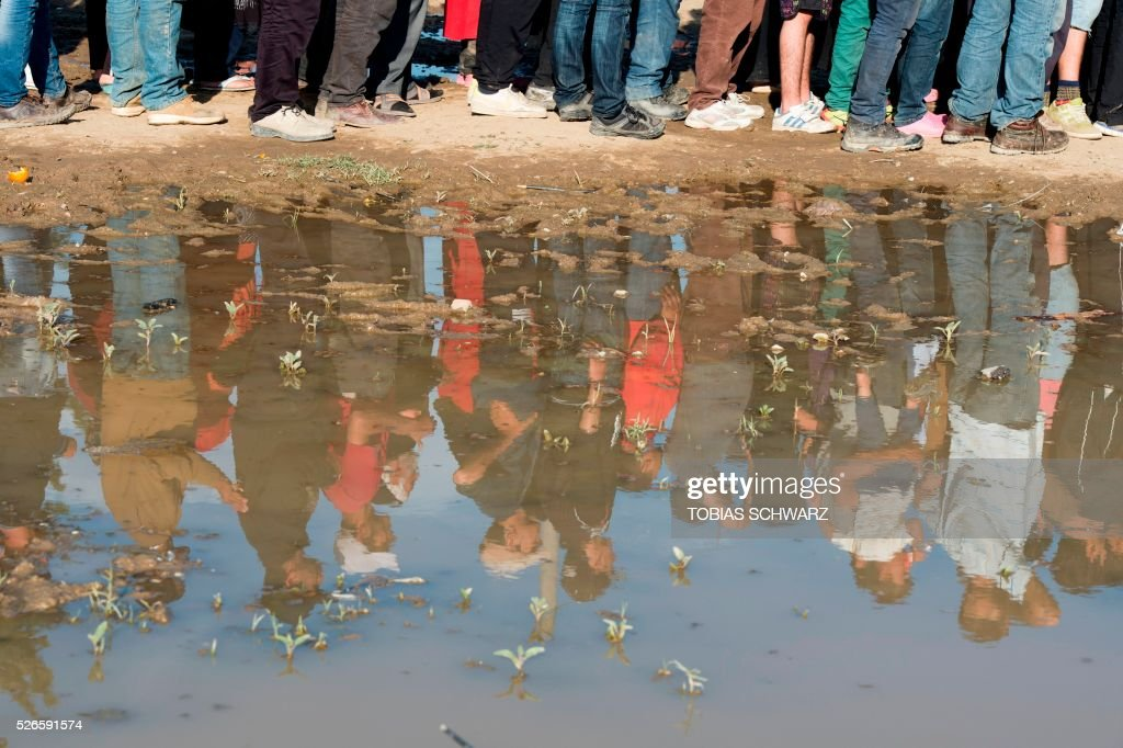 People are reflected in a puddle as they queue for fire wood at a makeshift camp for migrants and refugees near the village of Idomeni not far from the Greek-Macedonian border on April 30, 2016. Some 54,000 people, many of them fleeing the war in Syria, have been stranded on Greek territory since the closure of the migrant route through the Balkans in February. / AFP / TOBIAS