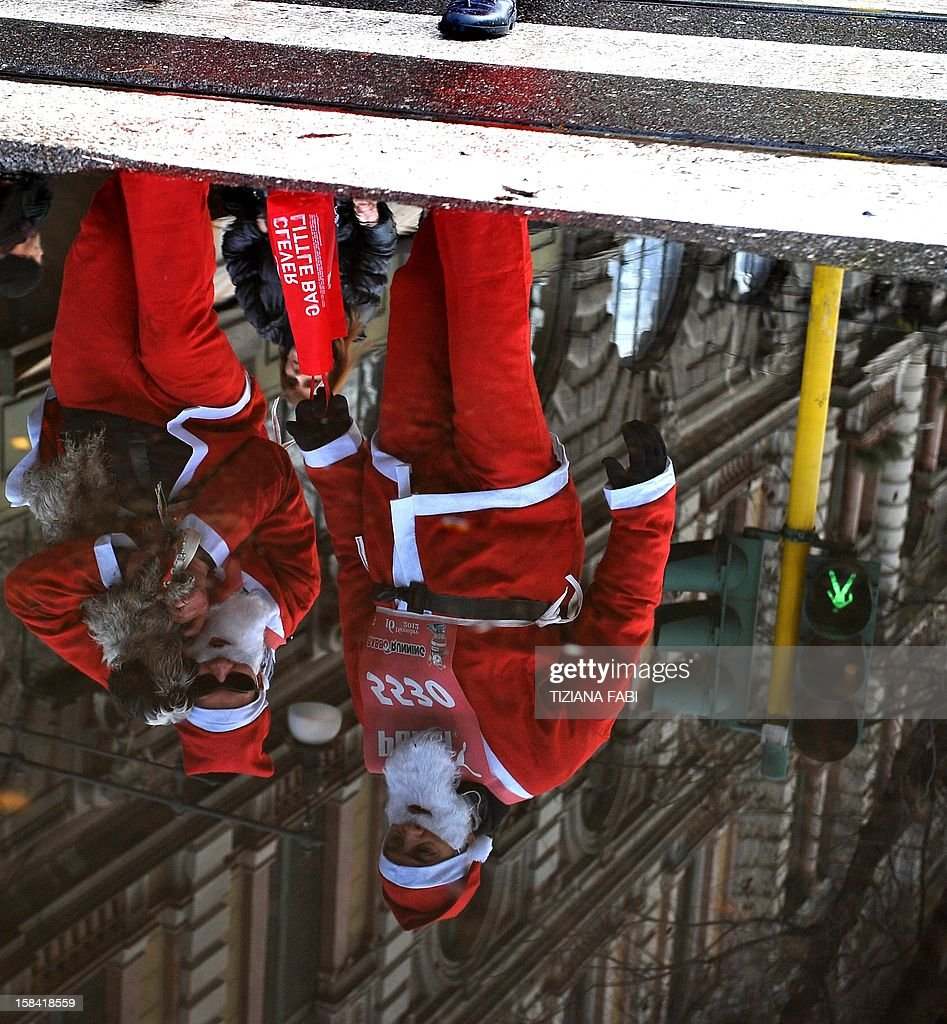 People are reflected in a puddle as they take part in a Santa Claus race in the center of Milan on December 16, 2012.