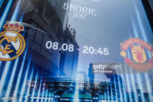 People are reflected in a Uefa Super Cup banner displayed at the fan zone in Skopje on August 7 one day ahead of UEFA Super Cup match between Real...