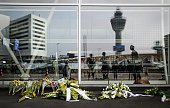 People are reflected in a window as the stand in front of flowers laid at the departure hall 3 at the airport in Schiphol the Netherlands on July 17...