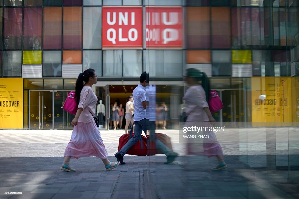 People are reflected in a window as they walk past a shopping mall in Beijing on July 13, 2015. China's total trade slumped in the first half of this year, official data showed on July 13, falling well short of the government's targets and dealing a blow to the global economy from its biggest trader in goods.