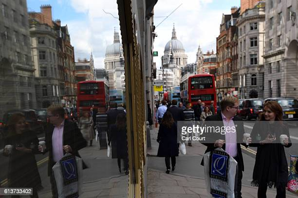 People are reflected in a window as they walk past the Goldman Sachs investment offices in Peterborough Court on October 10 2016 in London England A...
