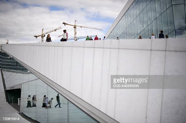 People are reflected in the entrance as others climb up to the roof of the Opera house in Oslo on August 11 2011 The building with it's interactive...