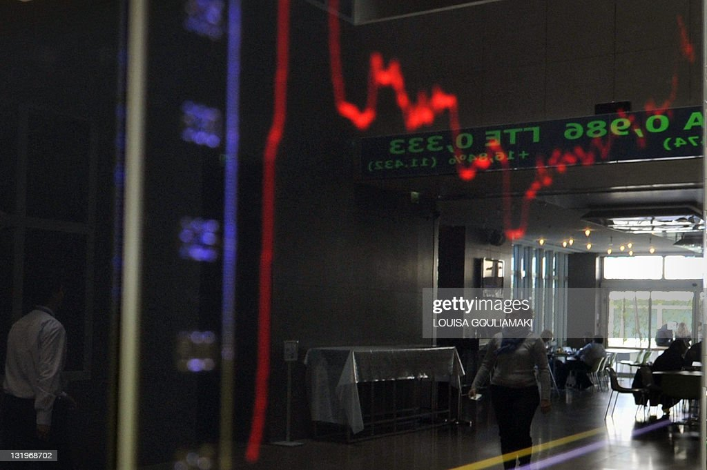 People are reflected in the index board at the Athens stock exchange on October 27 2011 Greece reacted with measured relief on Thursday after...