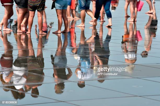 People are reflected in the 'Mirroir d'eau' a reflecting pool of water in Bordeaux where temperatures came close to 40 C on July 18 2017 / AFP PHOTO...