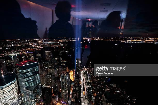 People are reflected in the window of the observatory in One World Trade Center as the 'Tribute in Light' illuminates the night sky of Lower...
