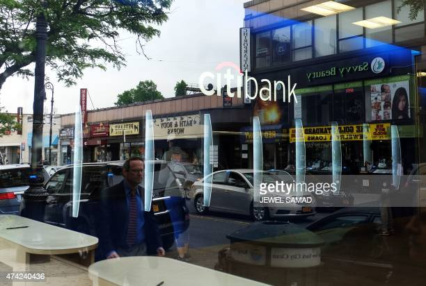 People are reflected on a glass window as they walk past a branch of Citibank in New York on May 21 2015 US and British regulators fined six major...