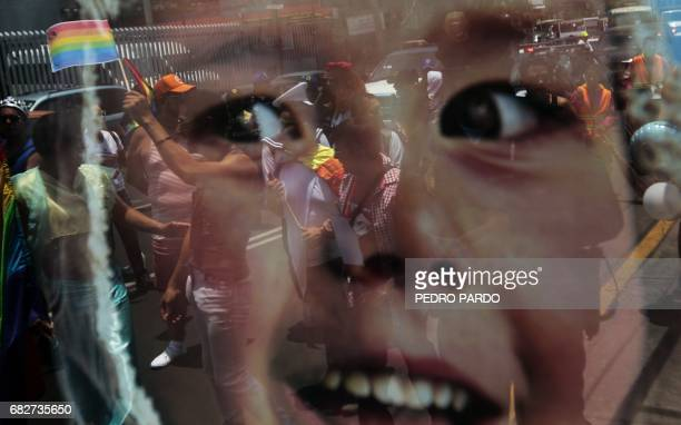 People are reflected on a window as they take part in the Lesbian Gay Bisexual Transsexual and Transgender Pride Parade in Iztapalapa in Mexico City...