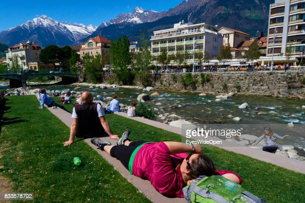 People are relaxing in the sun at the Etsch river in the green city centre of Meran in South Tyrol on April 21 2015 in Lana Italy