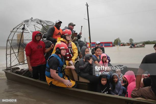 People are rescued from a flooded neighborhood after it was inundated with rain water remnants of Hurricane Harvey on August 28 2017 in Houston Texas...