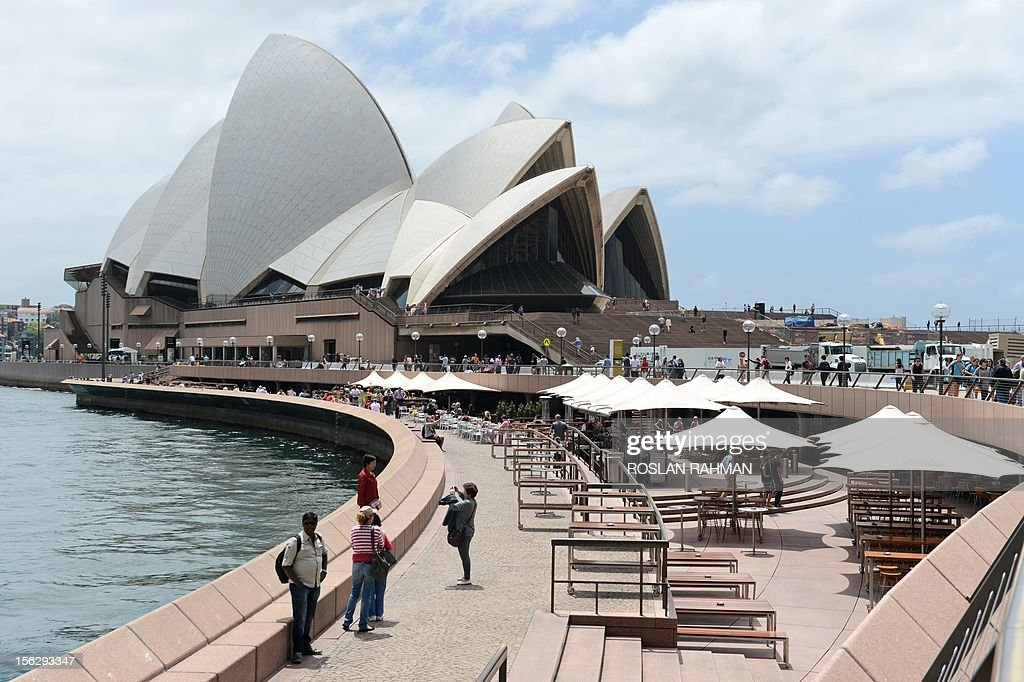 People are seen along the Circular Quay leading to Sydney's Opera House (background) on November 13, 2012.