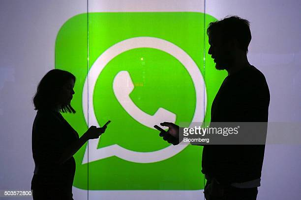 People are seen as silhouettes as they check mobile devices whilst standing against an illuminated wall bearing WhatsApp Inc's logo in this arranged...