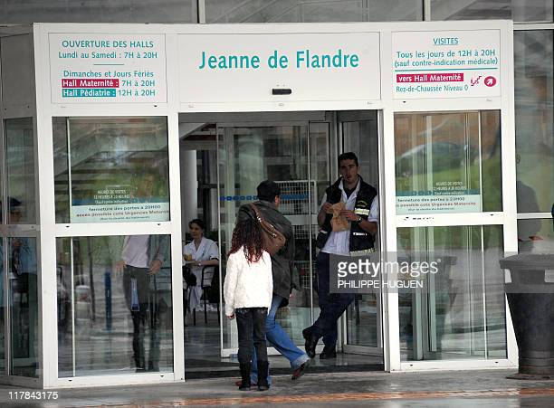 People are seen at the entrance of the hospital Jeanne de Flandre where six children were being treated on June 16 2011 in the northern French town...