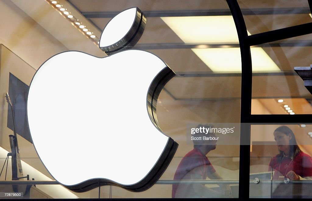 People are seen behind the Apple logo in Apple's flagship London retail store on Regent Street on December 27 2006 in London England With many stores...