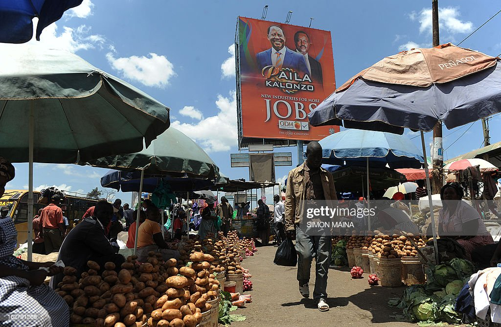 People are seen in a market place next to a campaign billboard advertising presidential candidate Raila Odinga (L) and his running mate Kalonzo Mosyoka in Nairobi on February 27, 2013. Kenya is gearing up for presidential, gubernatorial, senatorial elections on March 4, the first since bloody post-poll violence five years ago in which more than 1,100 people died after contested results.