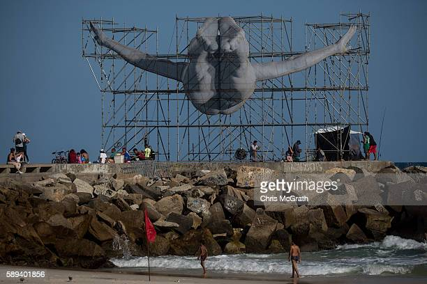 People are seen in front of a large sculpture created by artist JR on the seaside on August 13 2016 in Rio de Janeiro Brazil The artist JR has...