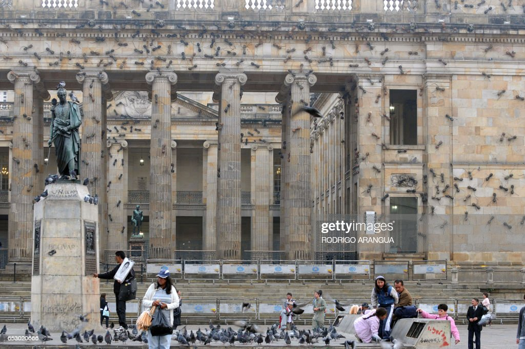 People are seen in front of Colombia's National Congress which is covered with sculptures of large ants - a work by Colombian artist Rafael Gomezbarros - in Bogota on February 16, 2010. Gomezbarrios said the ants symbolize the people displaced by armed conflict in Colombia. AFP PHOTO/ Rodrigo ARANGUA /