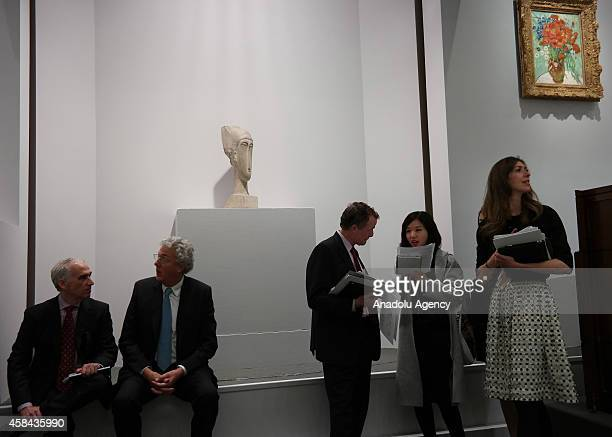 People are seen in front of the Amadeo Modigliani's Tête a rare stone carving sold for $707 million during an auction at Sotheby's in New York United...