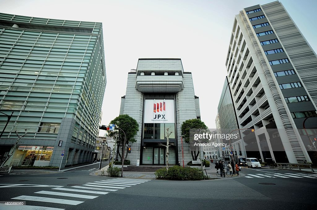 People are seen in front of the building of the Tokyo Stock Exchange in Tokyo Japan on February 16 2015 Japan's economy emerges from recession...