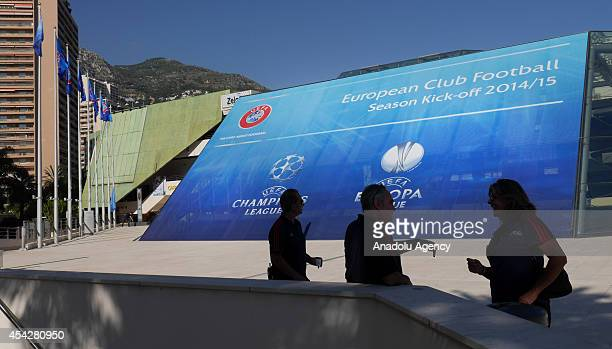 People are seen in front of the placard prior to the UEFA Champions League draw at the Grimaldi Forum building in Monaco on August 27 2014 The 32...