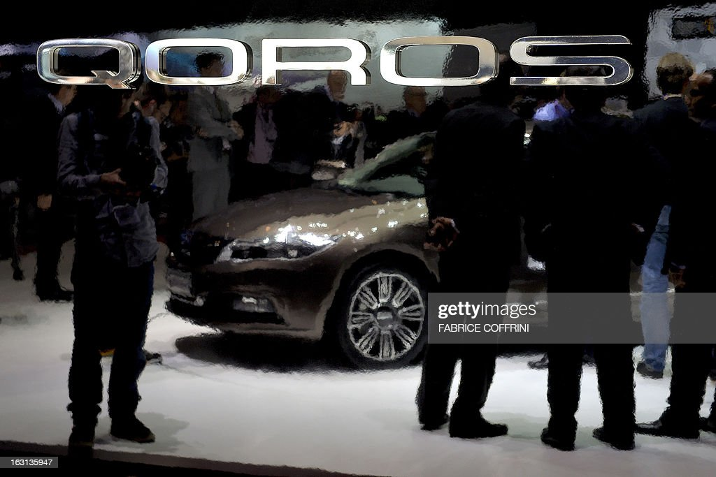 People are seen in the reflection of a sign for the Qoros 3 Sedan at the Chinese car maker's booth during the 83rd Geneva Motor Show on March 5, 2013 in Geneva. The Geneva International Motor Show opens its doors to the press today under a dark cloud, with no sign of a speedy rebound in sight for the troubled European market.