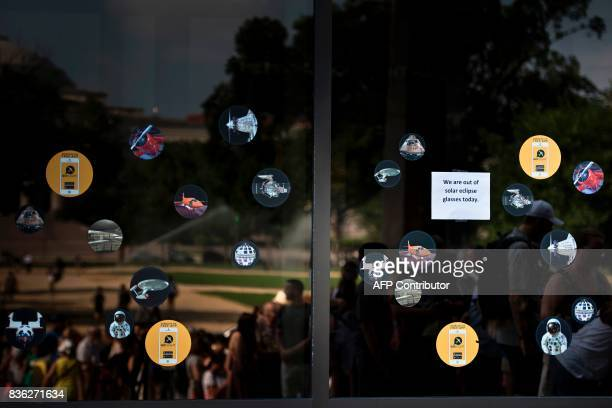 People are seen lining up outside the Smithsonian's Air and Space Museum as a sign indicates there are no more eclipse glasses on the National Mall...