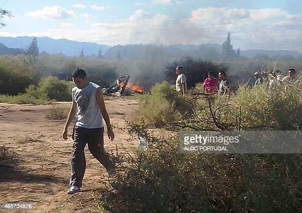 People are seen near the burning wreckages of two helicopters which collided midair near Villa Castelli in the Argentine province of La Rioja on...