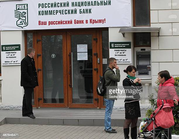 People are seen near the entrance of a newly opened branch of Russian National Commercial Bank on April 5 2014 in Sevastopol in the disputed Crimean...