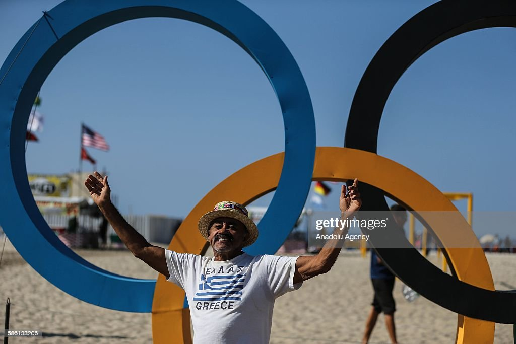 People are seen near the Olympics Rings at the Copacabana beach ahead of the start of the Rio 2016 Olympic and Paralympic Games in Rio de Janerio, Brazil on August 5, 2016.