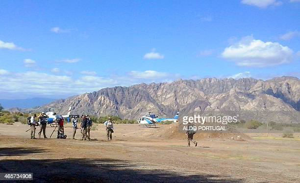 People are seen near the two helicopters which collided midair near Villa Castelli moments before the accident in the Argentine province of La Rioja...