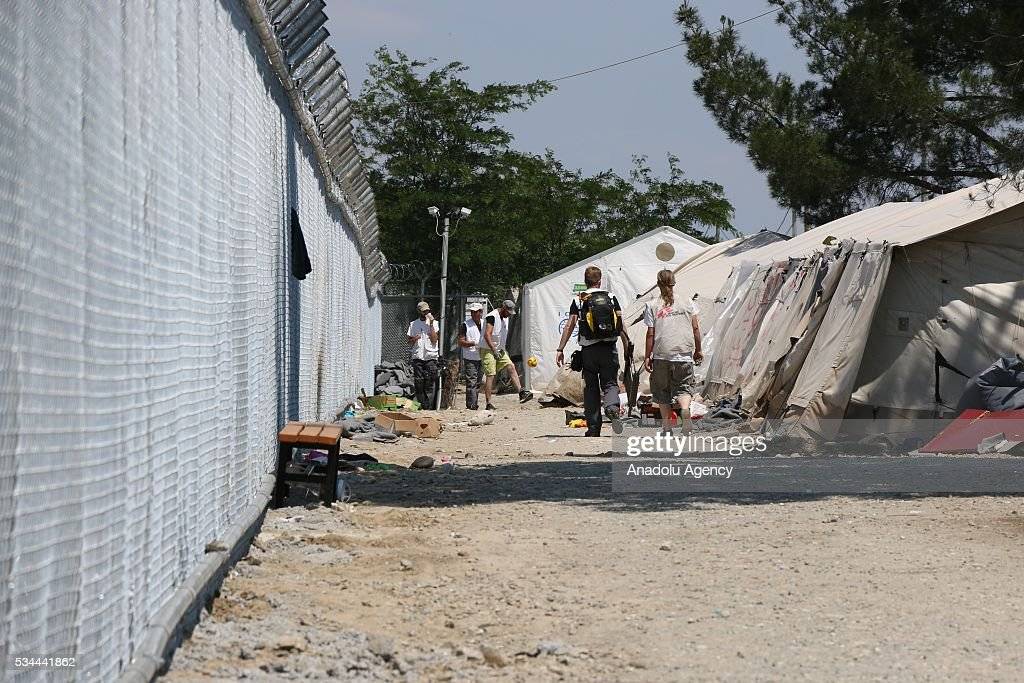 People are seen next to tents as more than 8.000 refugees evacuated to another camp in Idomeni refugee camp in Greece on May 26, 2016.