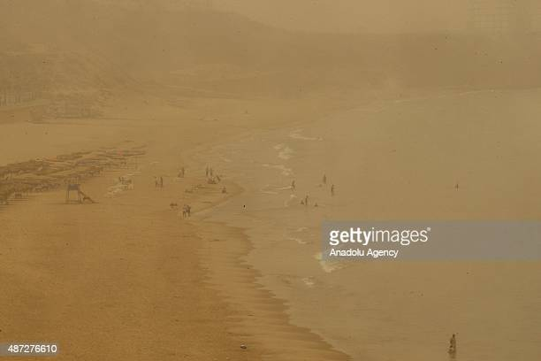 People are seen on a beach during a sand storm that hit Lebanon's Beirut on September 8 2015