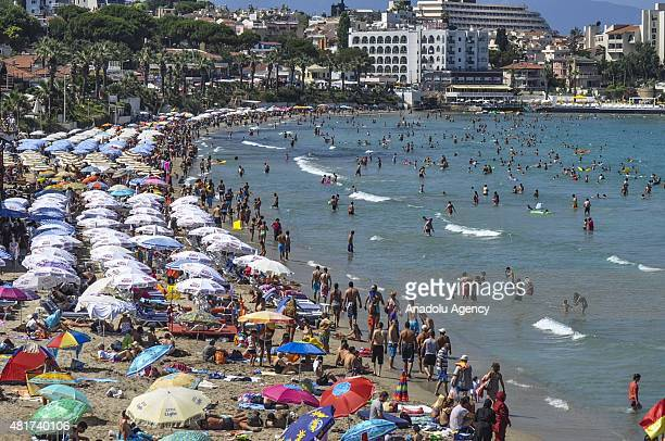 People are seen on a beach in one of the Turkey's Aydn Province's touristic districts Kusadasi on July 24 2015 People cool themselves off by swimming...