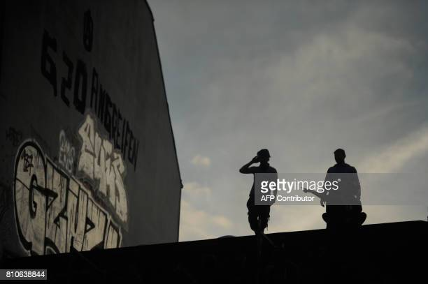 People are seen on a roof next to a wall with the inscription 'Attack G20' during protests in Hamburg's Schanzenviertel district on July 7 2017 in...