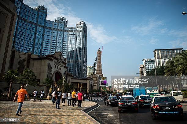 People are seen outside the Studio City casino ahead of its opening in Macau on October 27 2015 Casino operator Melco Crown was to open its latest...