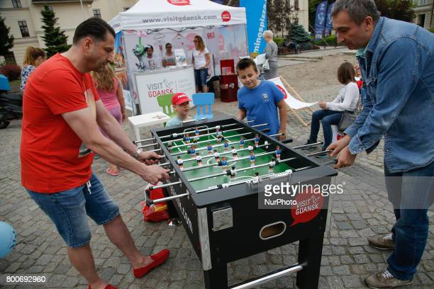 People are seen playing table football at a promotion stand for the city Gdansk in the center of Bydgoszcz Poland A Toyata car with both petrol...